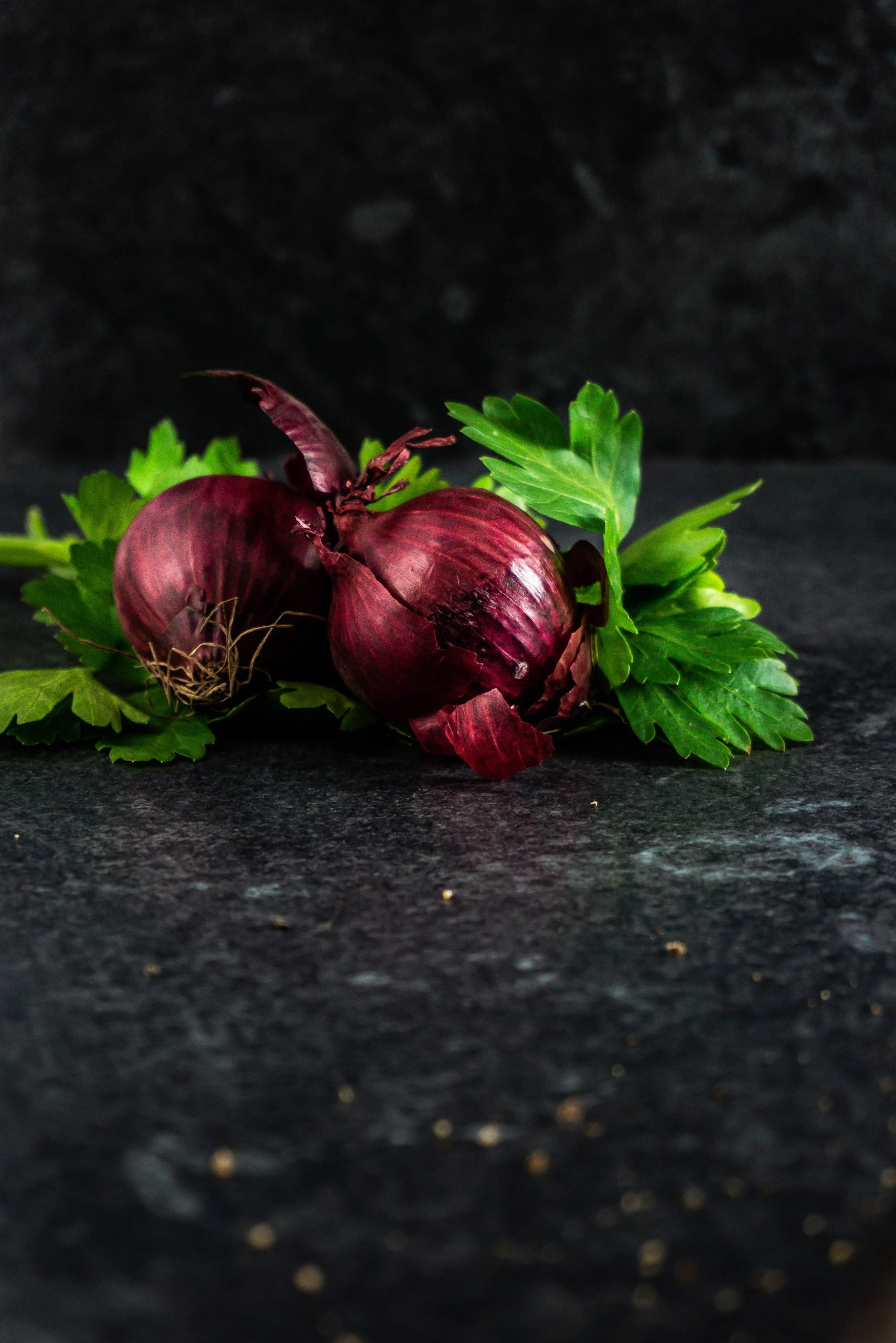 Red onion and parsley on a dark background