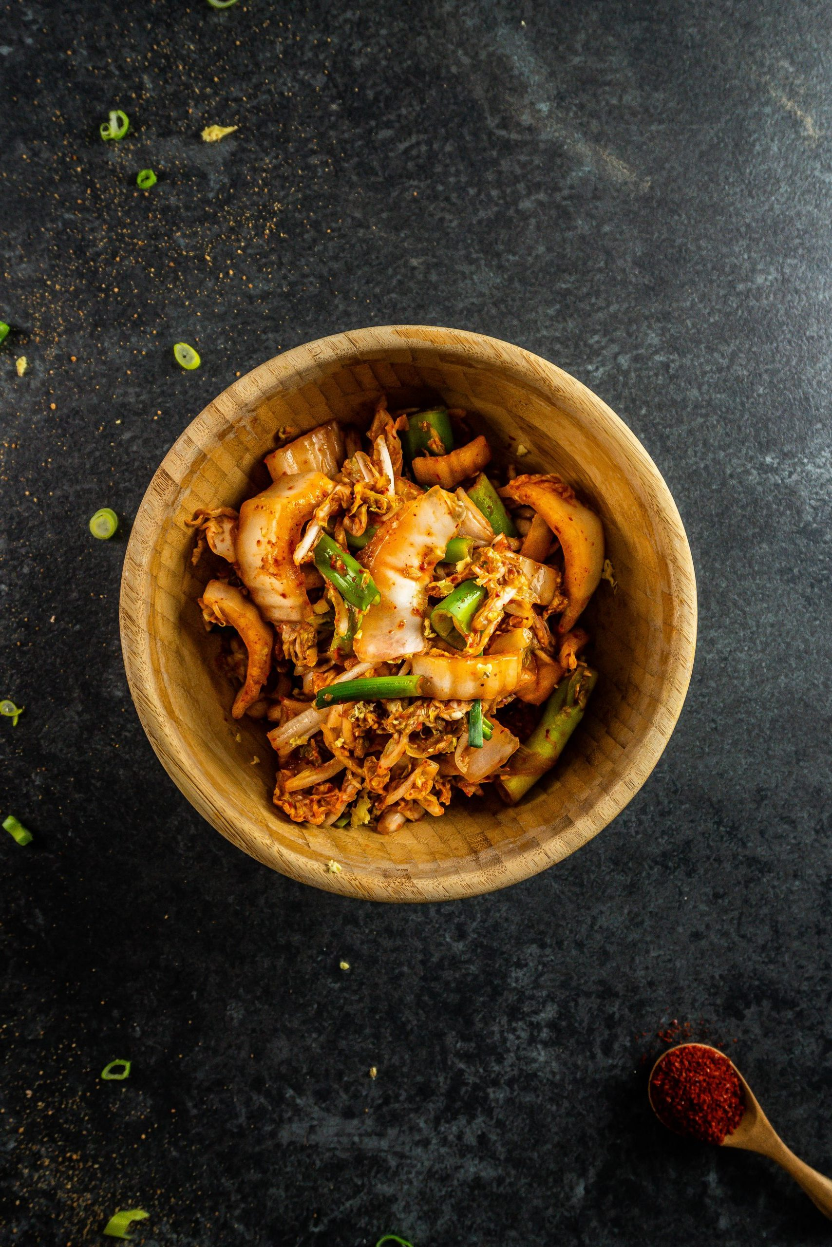 Delicious Vegan Kimchi in a wooden bowl on a dark background photographed from above