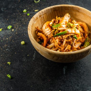 Delicious Vegan Kimchi in a wooden bowl on a dark background