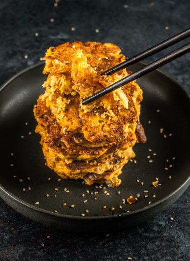 Korean-style Kimchi Pancakes (Kimchi Jeon) stacked on a plate with one bite being taken away by chop sticks