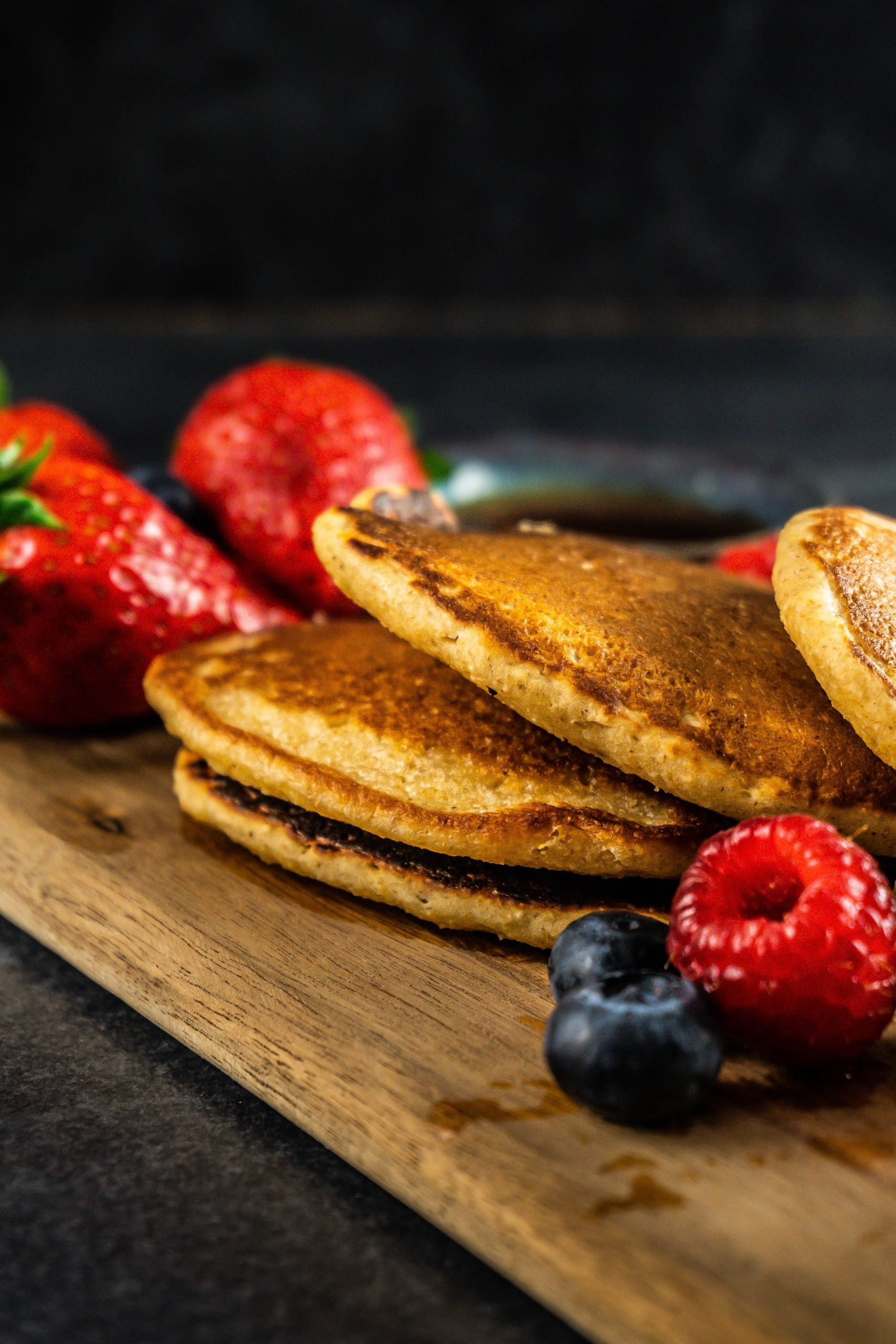 A stack of Fluffy Lemon Buttermilk Pancakes on a wooden board