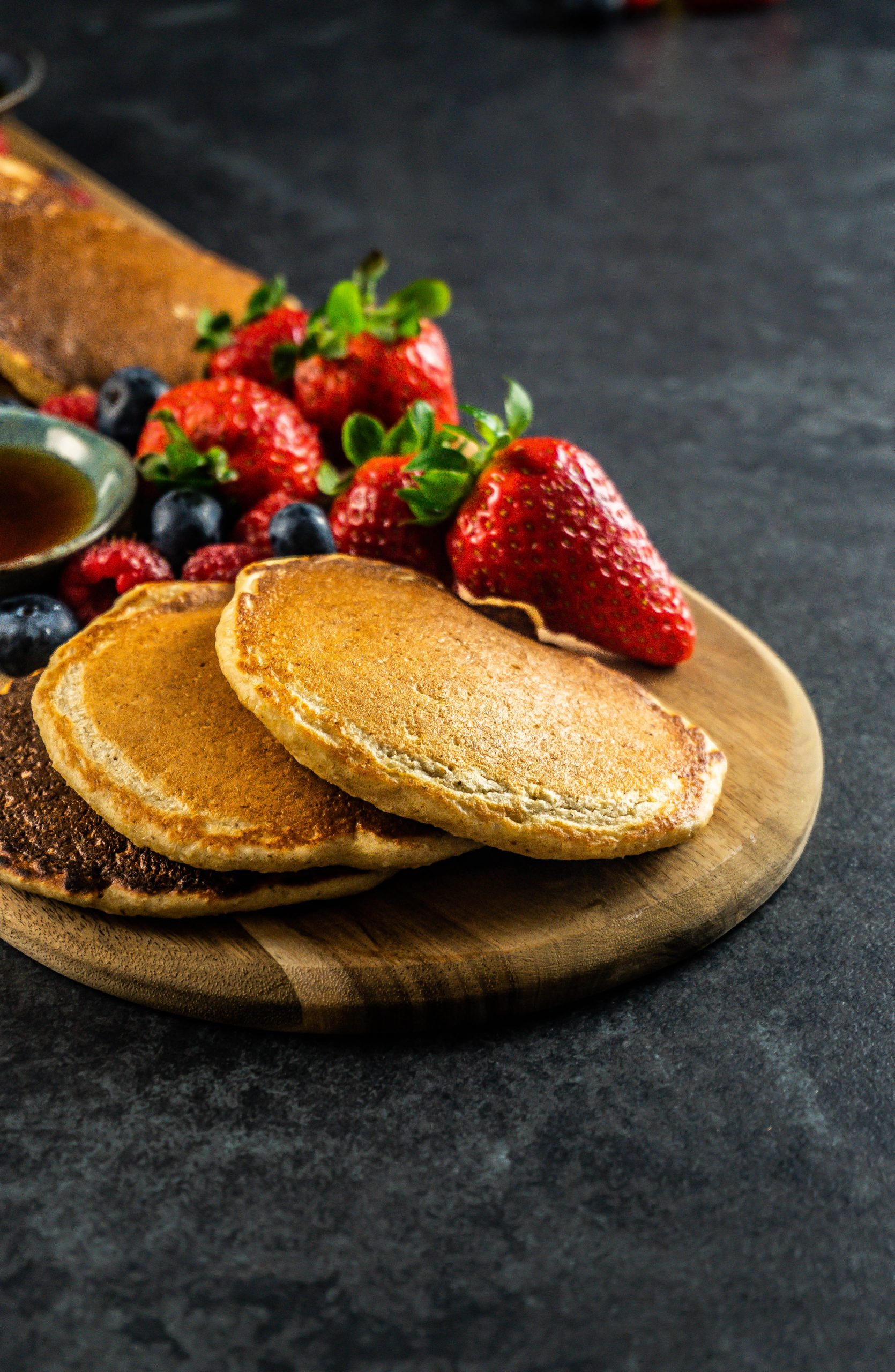 Fluffy Lemon Buttermilk Pancakes on a wooden board with different kinds of berries visible in the background and some maple syrup