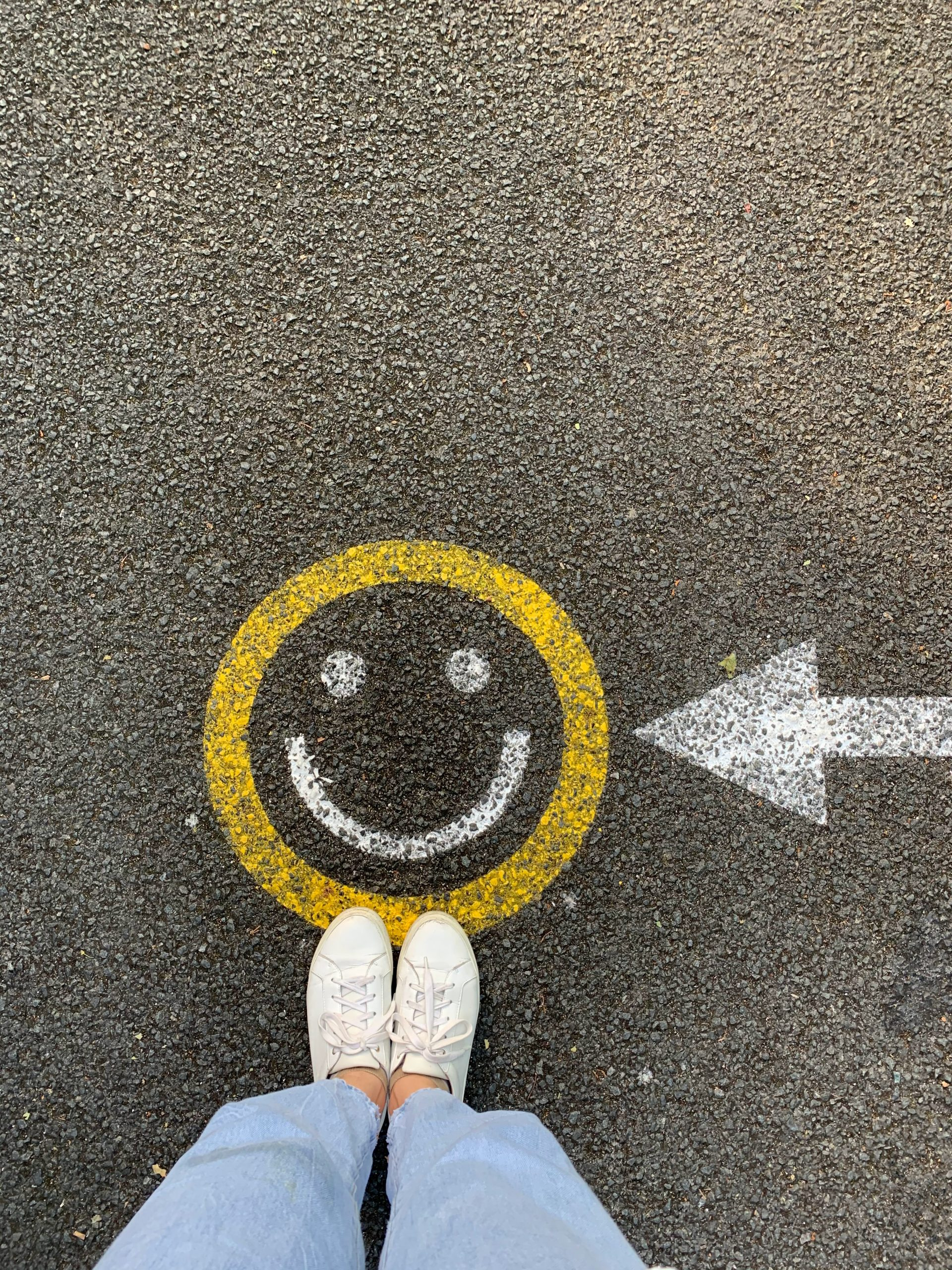 Woman standing at the feet of a smiley