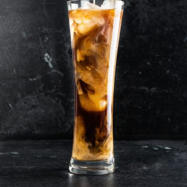 Cold coffee in a tall glass with ice cubes with milk running into the glass