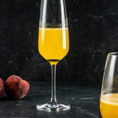 Easy Peach Bellini Cocktail in a champagne glass with peaches surrounding in the background