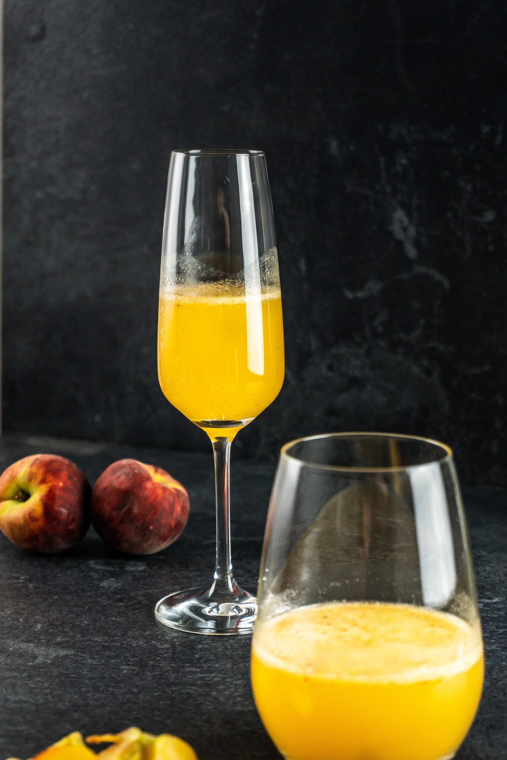 Easy Peach Bellini Cocktail in a champagne glass and a round glass with peaches in the background