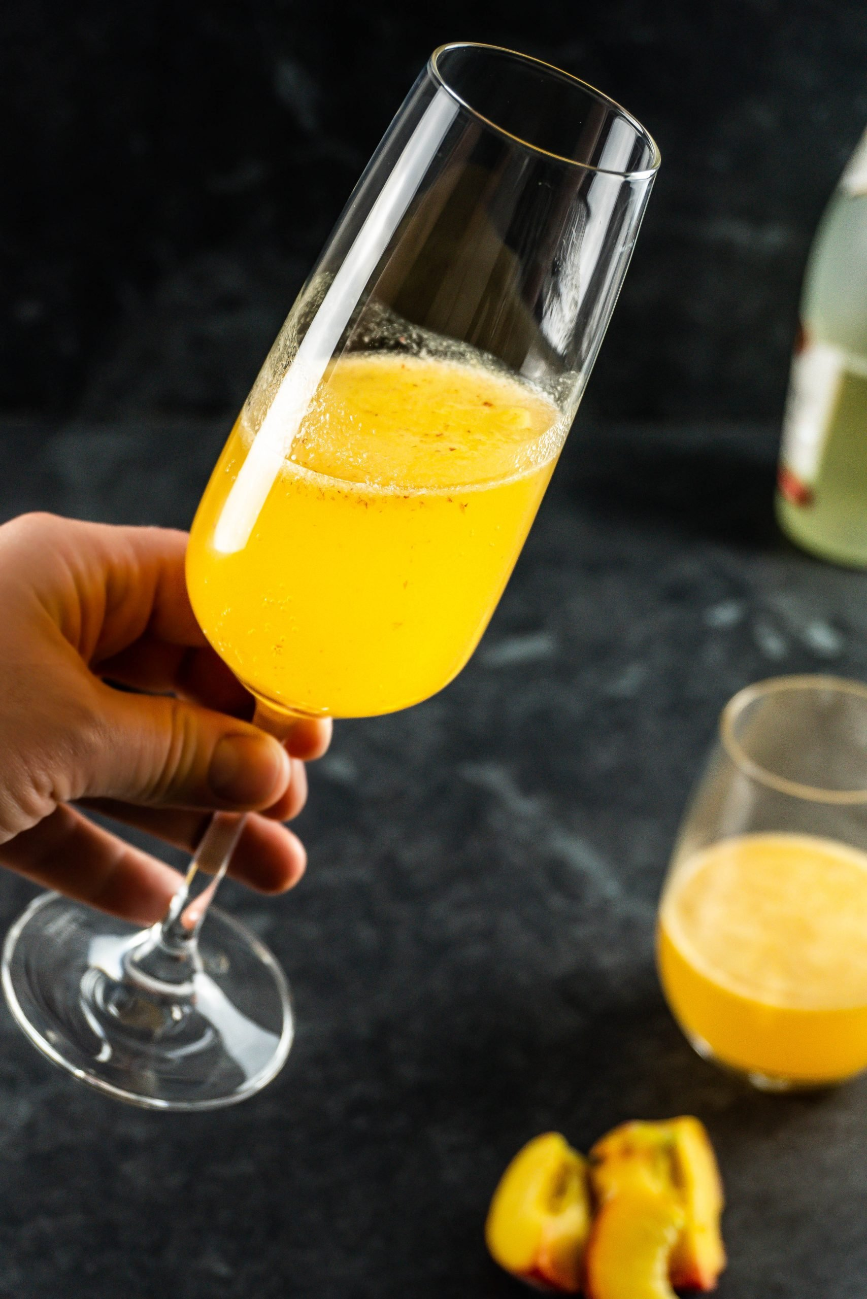 Easy Peach Bellini Cocktail in a champagne glass being held up close to the camera
