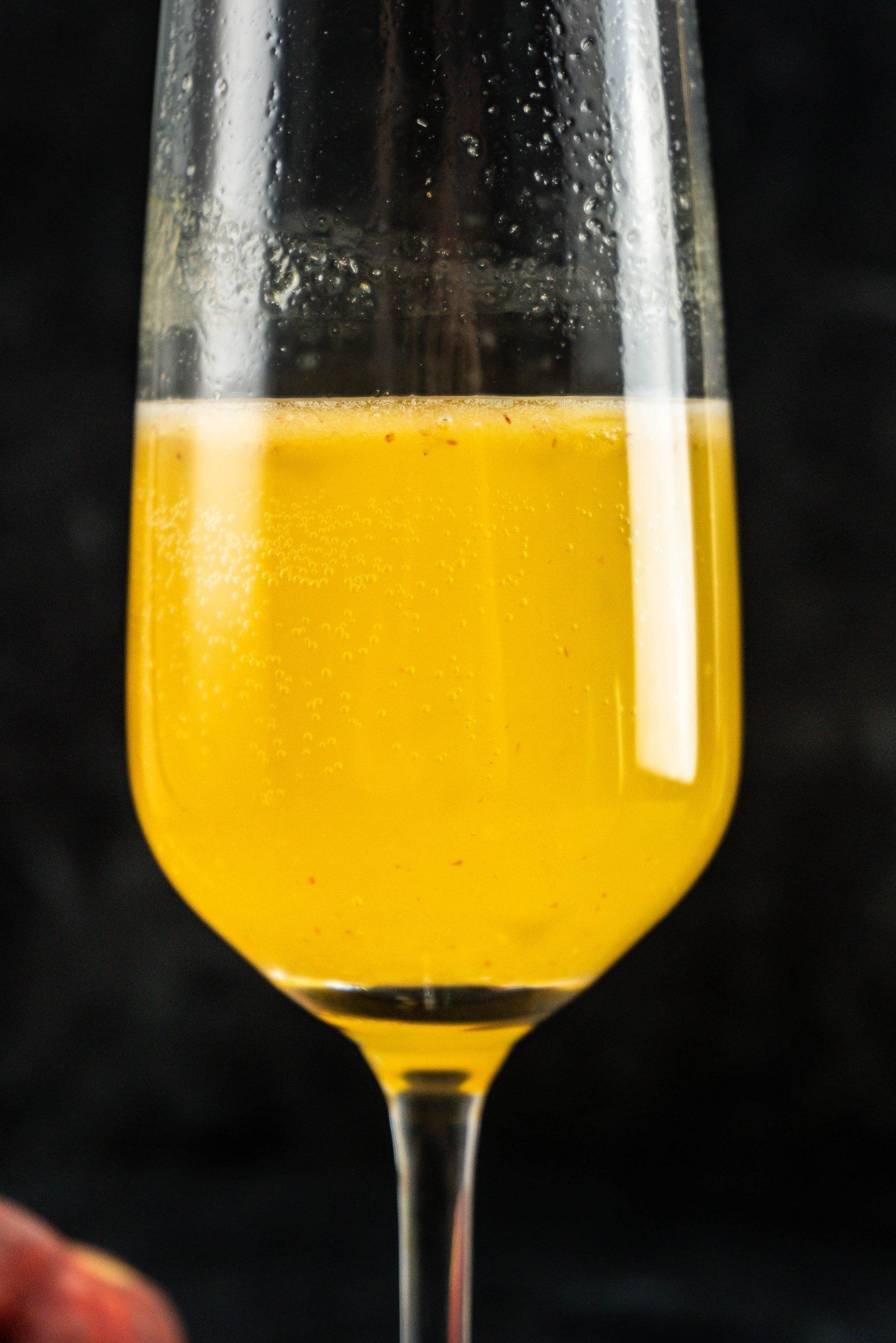 Close up of Easy Peach Bellini in a champagne glass close up