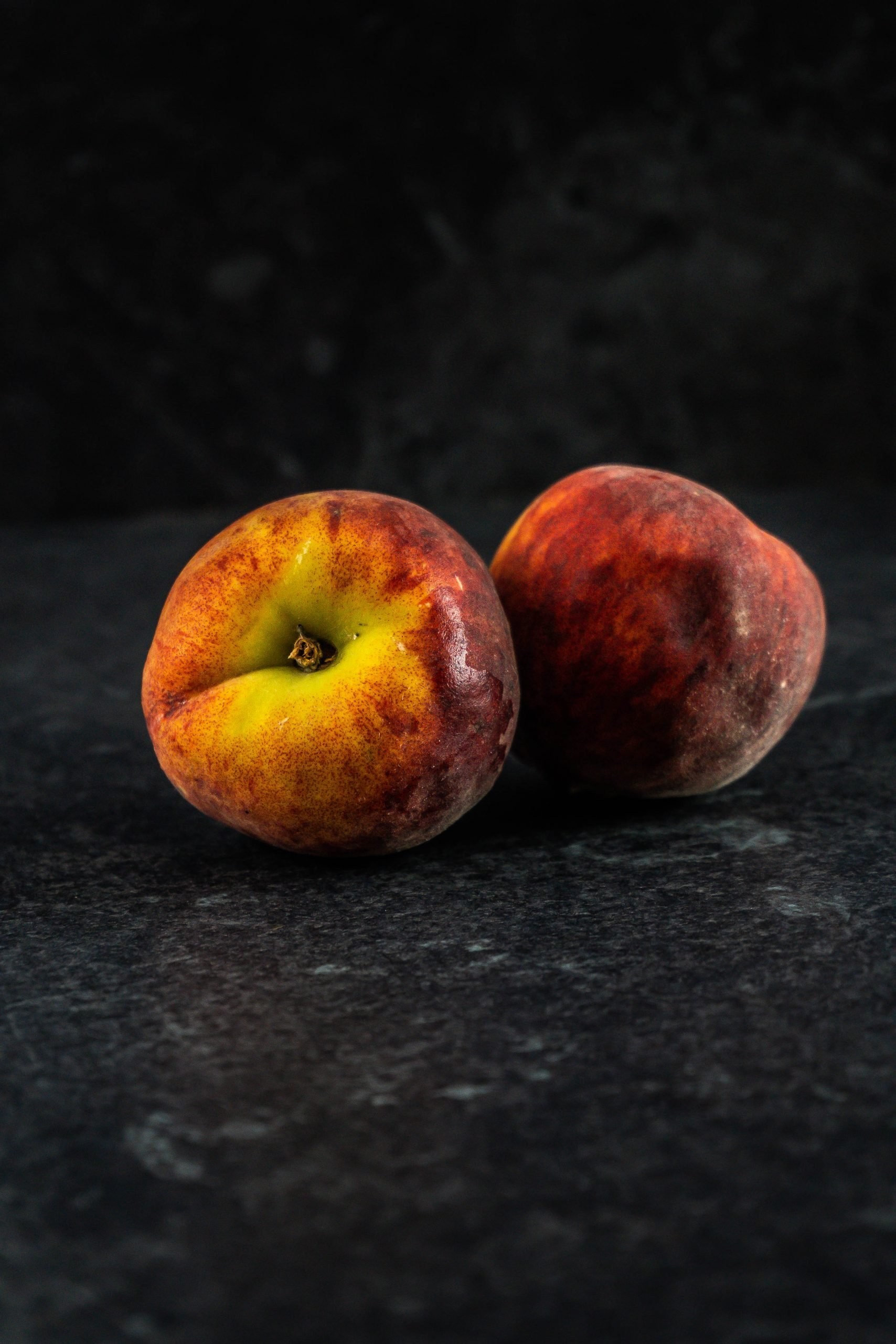 Two peaches on a dark background