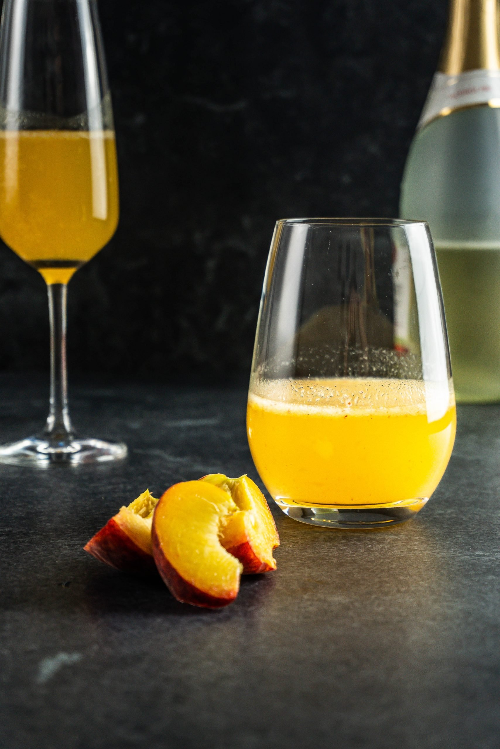 Easy Peach Bellini Cocktail in a champagne glass and a round glass with peaches and a bottle of champagne in the background