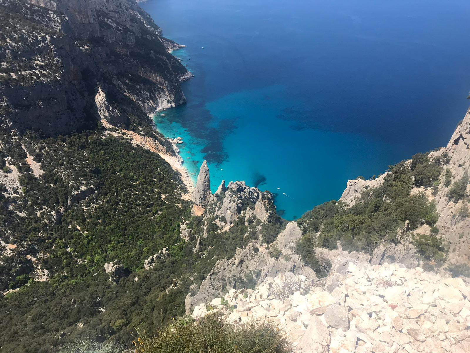 Aerial view down a mountain side to clear blue water in Sardinia