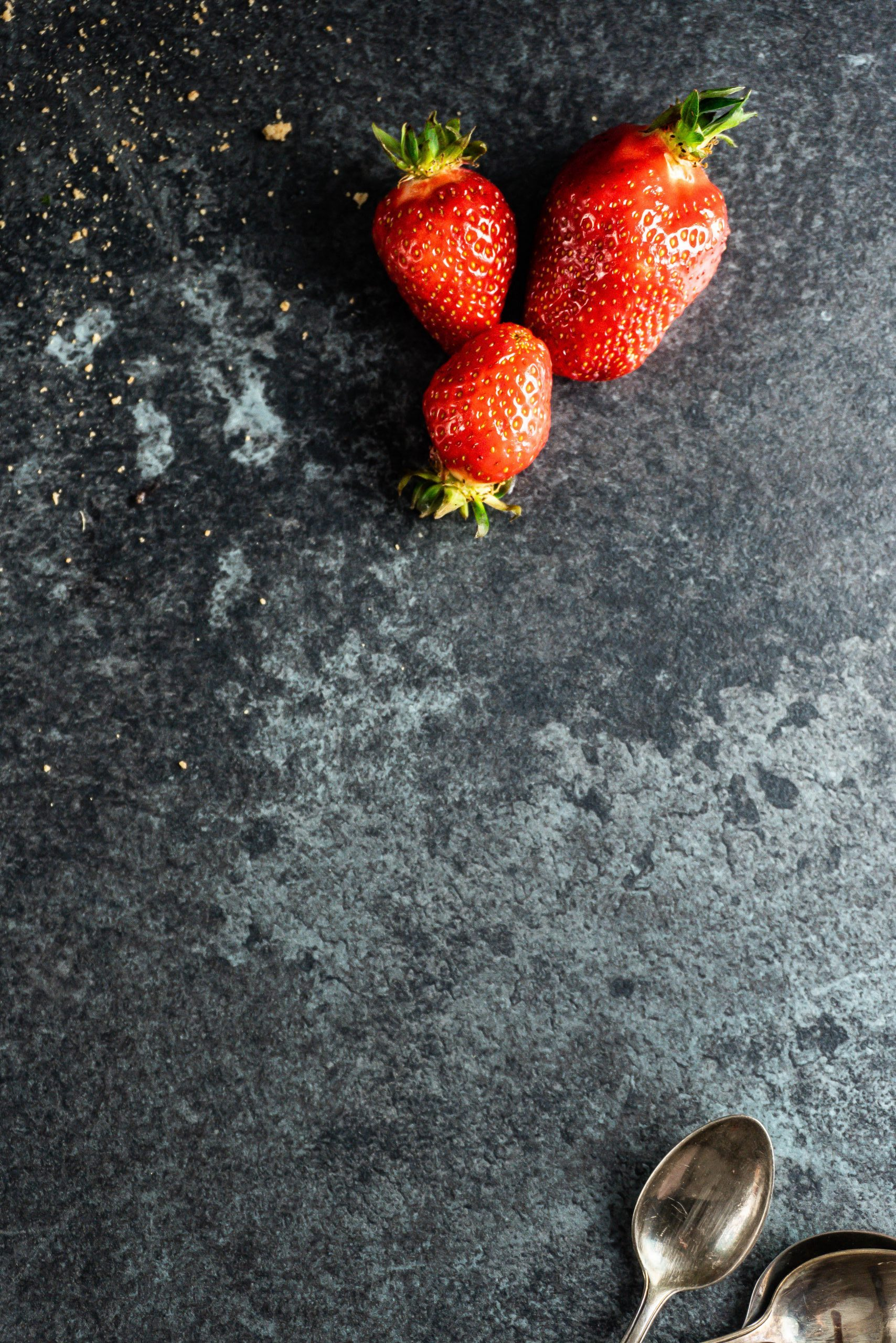 Strawberries photographed on a dark backround with dessert spoons sticking out in the corner