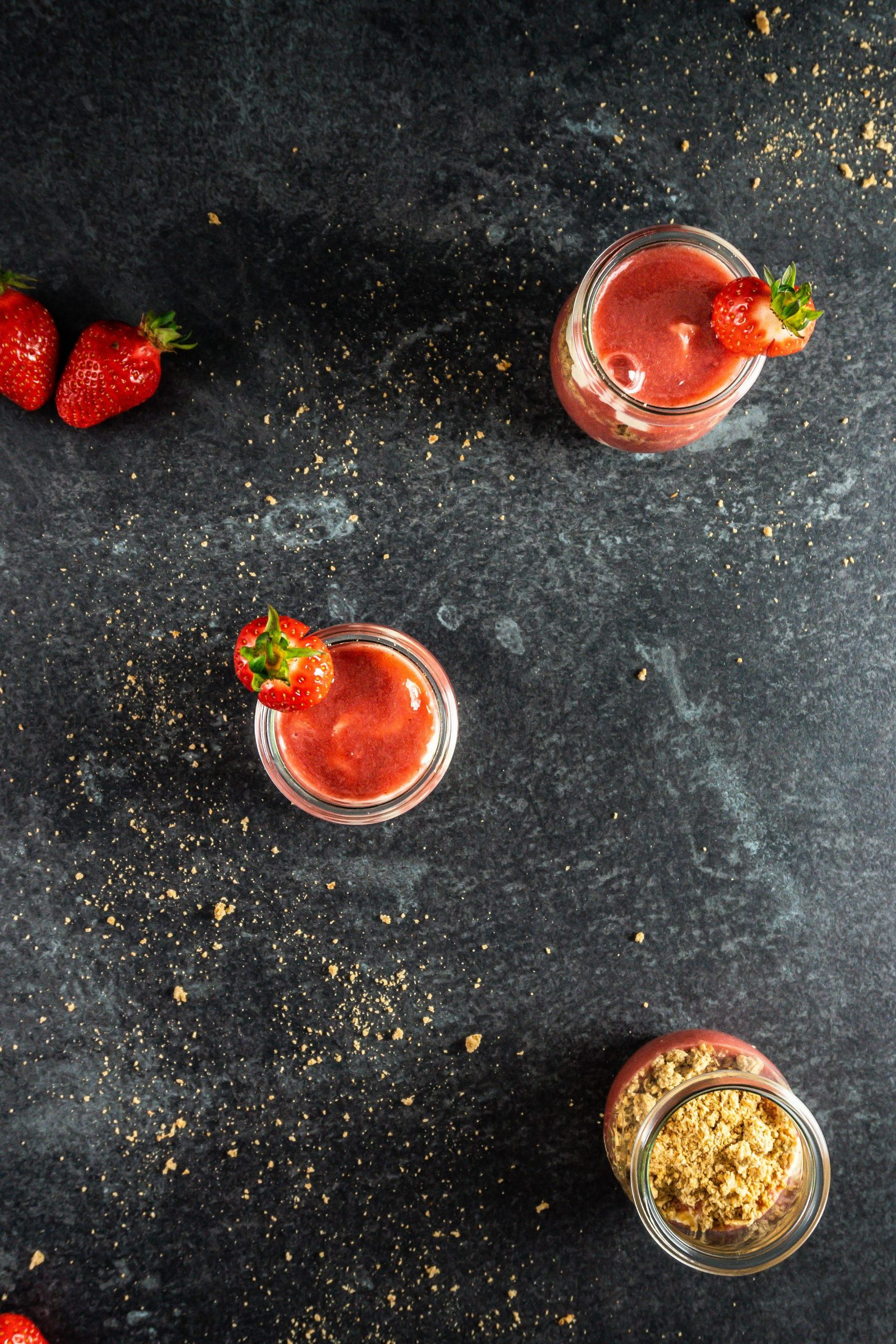 Three Strawberry Cheesecake Mini Desser Cups with decorated strawberries photographed on a dark background