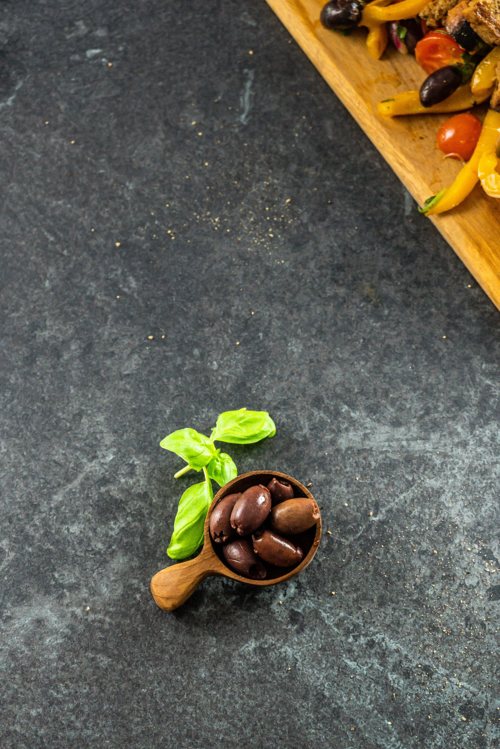 Olives in a wooden spoon with basil leaves on a dark surface
