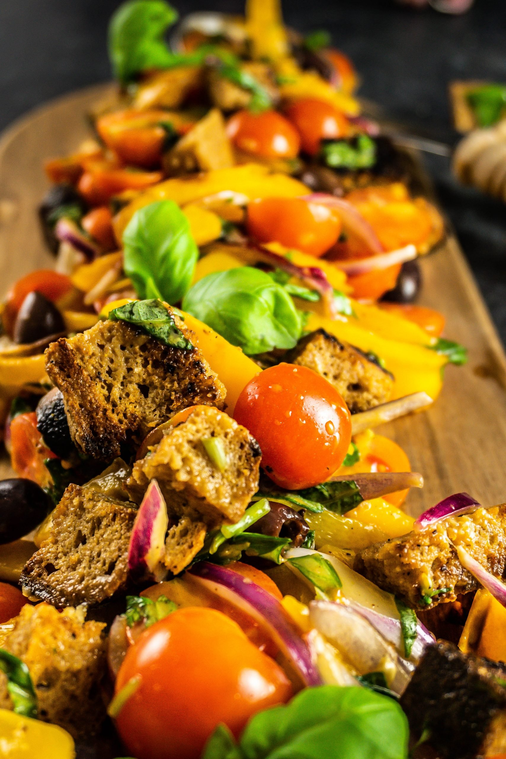 Tuscan-Style Bread and Tomato Salad (Panzanella) on a wooden board photographed up close