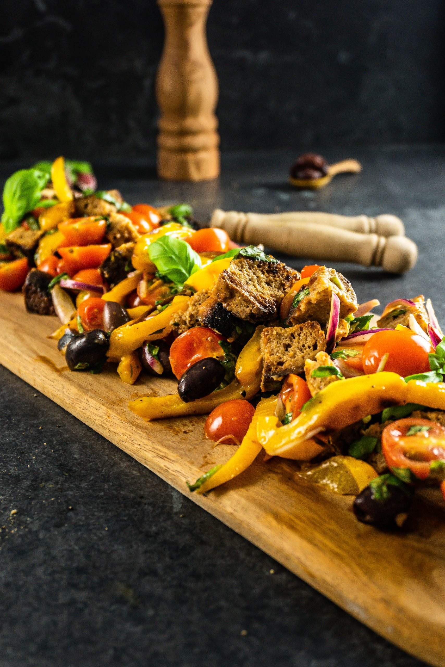 Tuscan-Style Bread and Tomato Salad (Panzanella) on a wooden board with tongs sticking out shot from a three-quarter angle