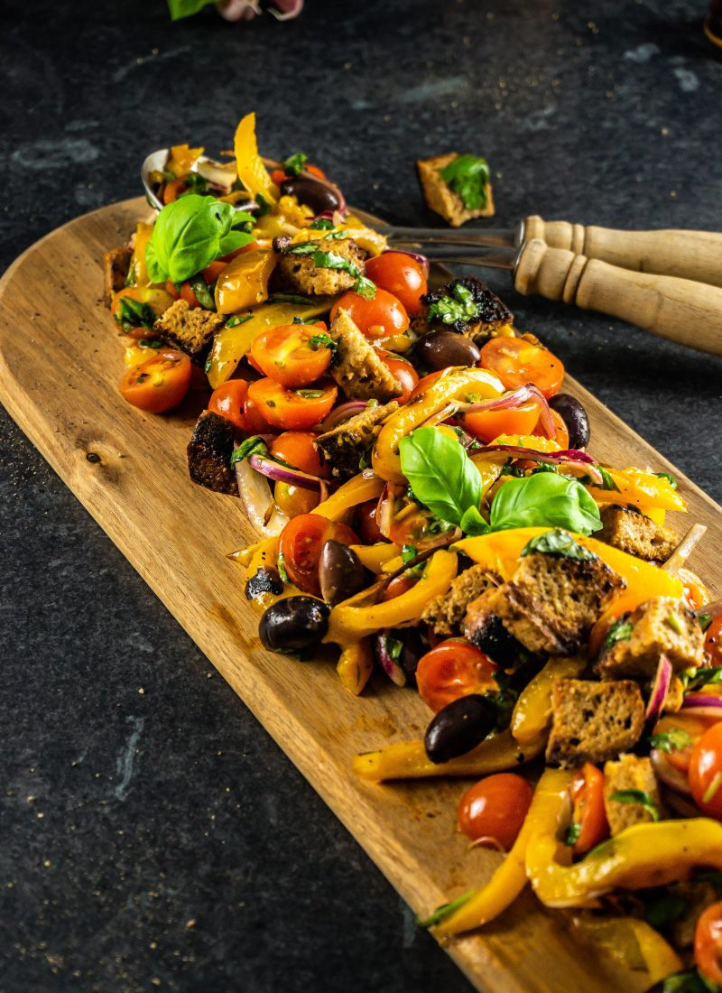 Tuscan-Style Bread and Tomato Salad (Panzanella) on a wooden board with salad tongs stuck into them