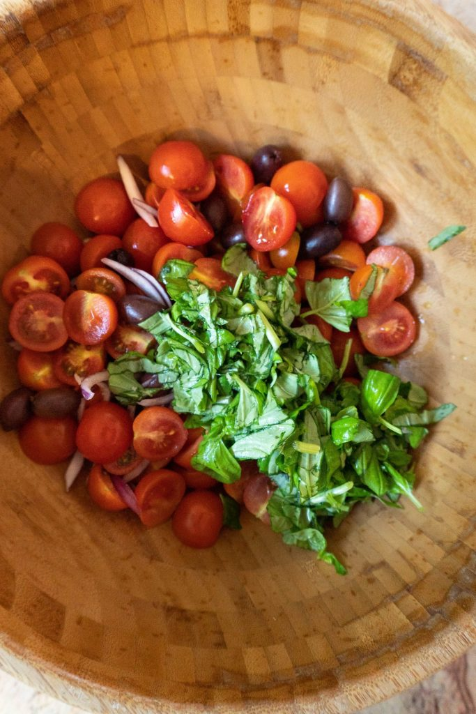 Halved cherry tomatoes, sliced onions, olives, and chopped basil in a wooden bowl