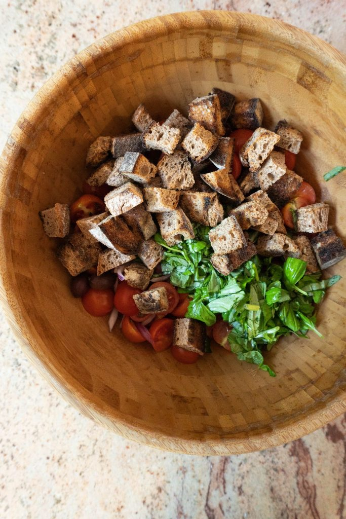 Halved cherry tomatoes, sliced onions, olives, chopped basil, and added bread pieces in a wooden bowl