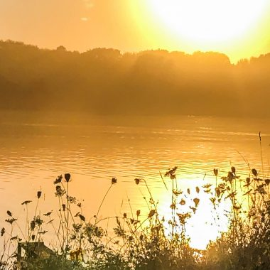 Sun setting over a lake basked in sunlight