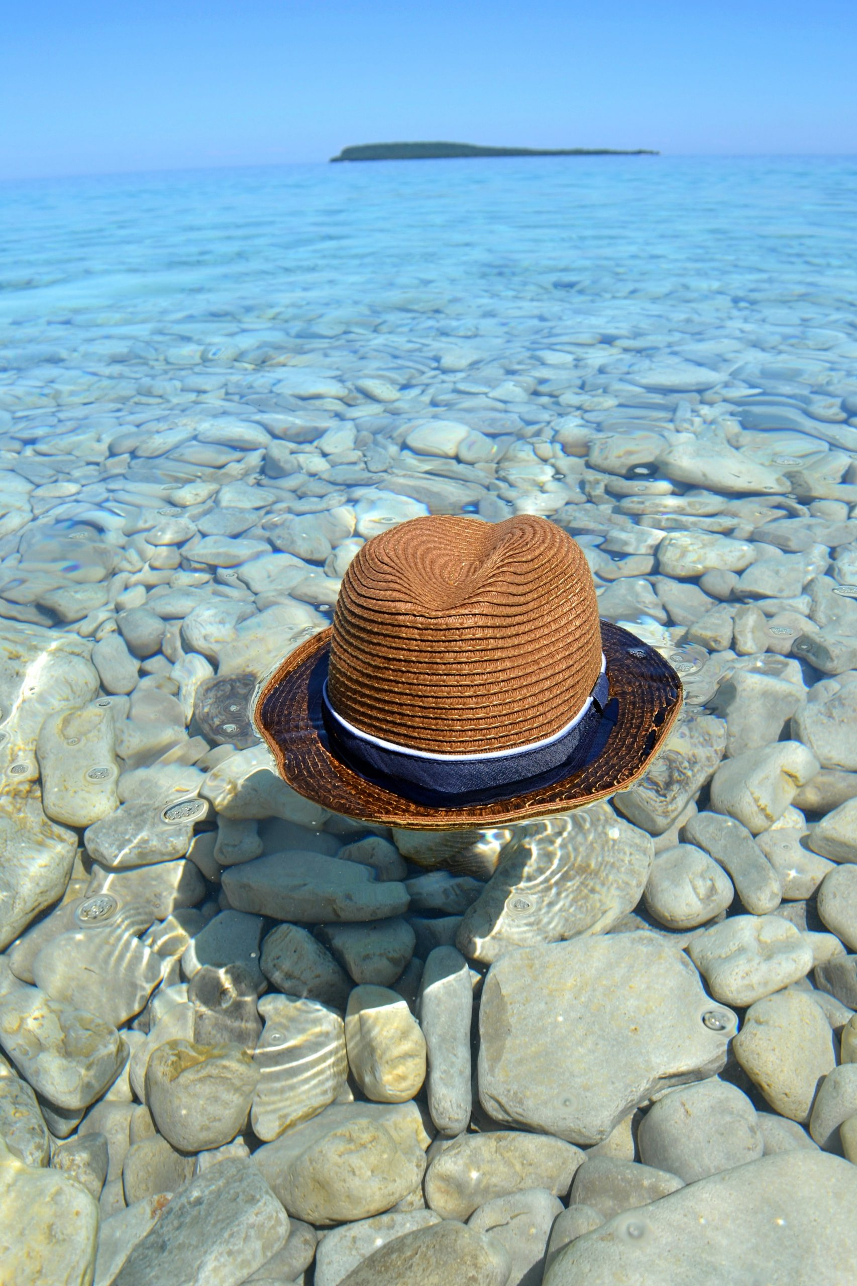 Hat swimming in clear water under stones