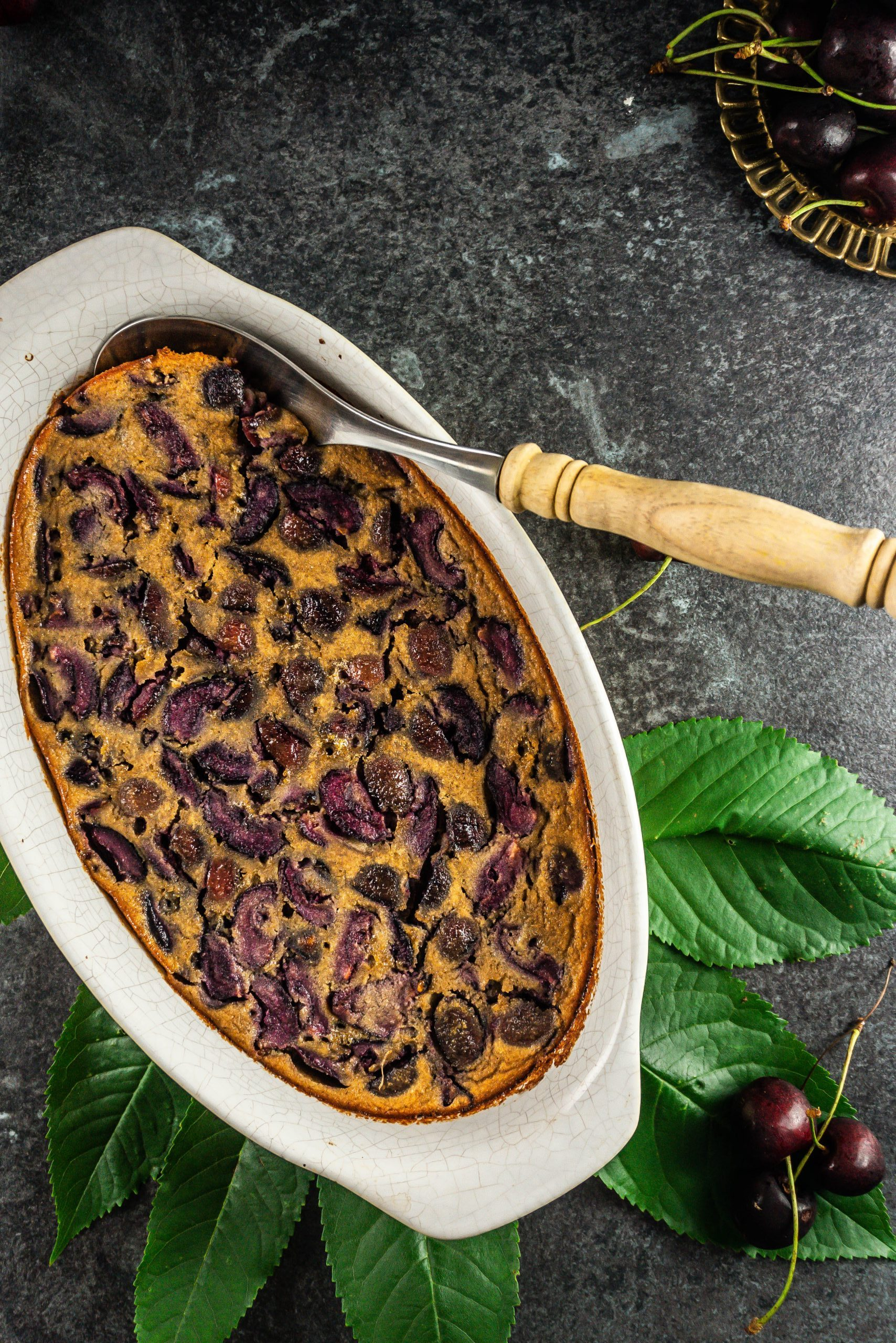 Cherry Clafoutis baked in a casserole dish with a serving spoon tucked into it and cherries lying around photographed from above