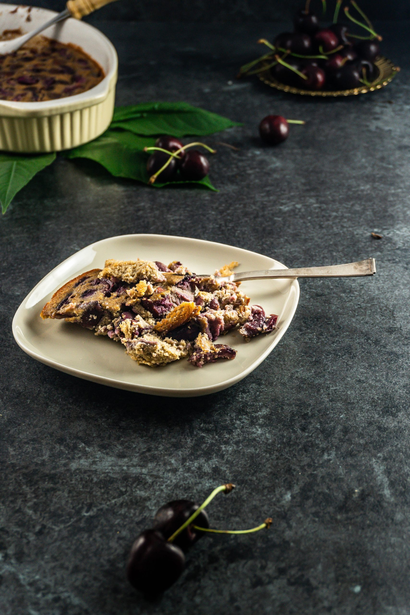 Cherry Clafoutis put on a plate with a fork tugged into with cherries lying around