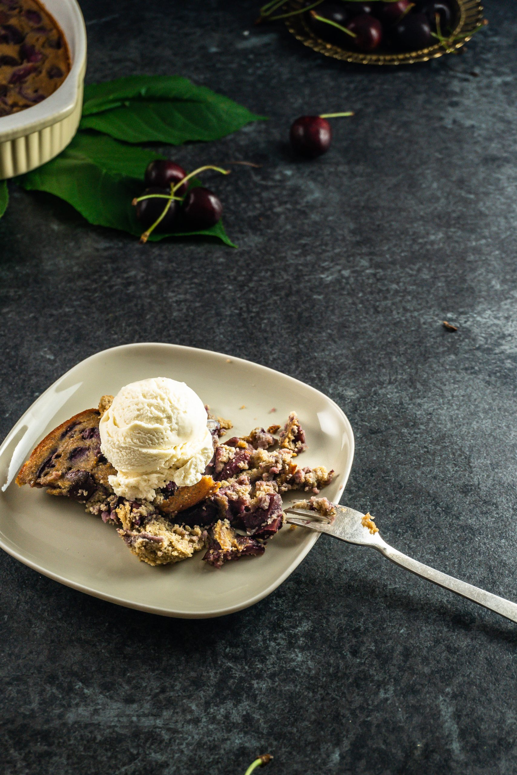 Cherry Clafoutis put on a plate with a fork tugged into and vanilla ice cream on top with cherries lying around