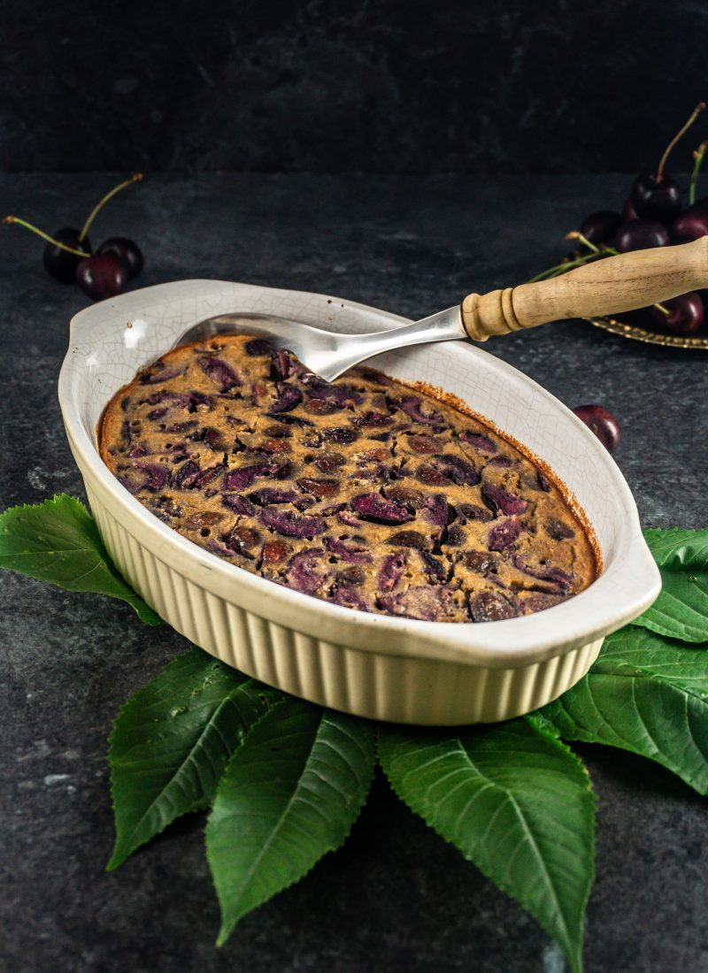 Cherry Clafoutis baked in a casserole dish with a serving spoon tucked into it and cherries lying around