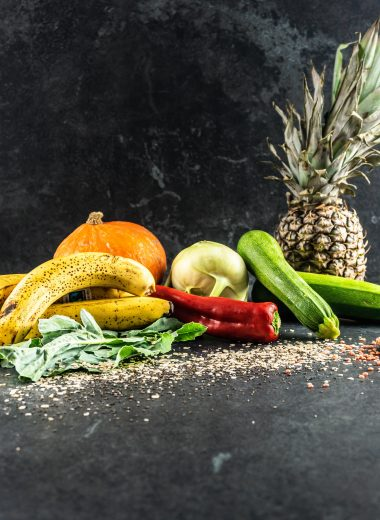 Bananas, pumpkin, kohlrabi, courgettes, peppers, oats, chia seeds, lentils, and a pineapple on on a black background