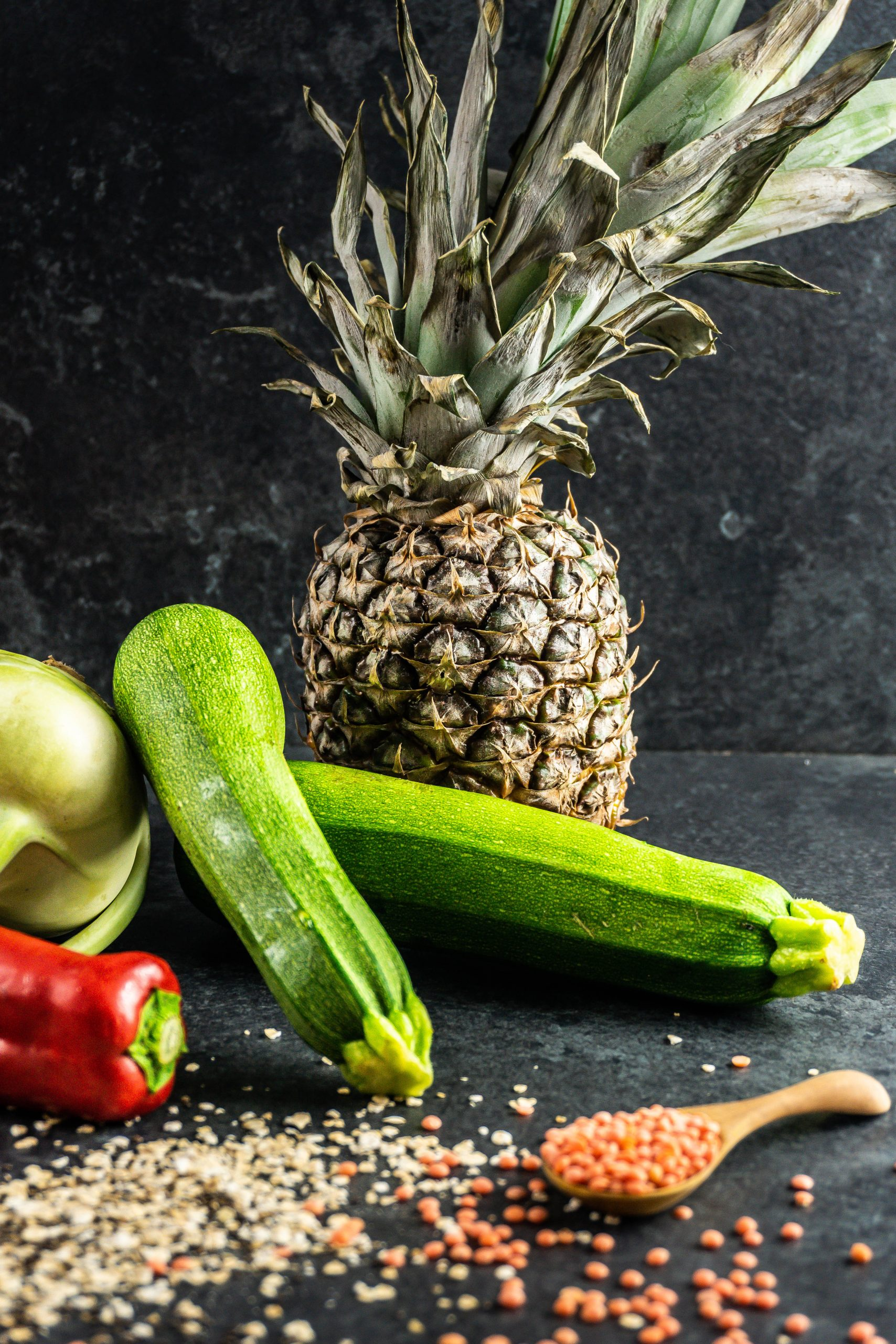 Courgettes and pineapple in focus, surrounded by other vegtables