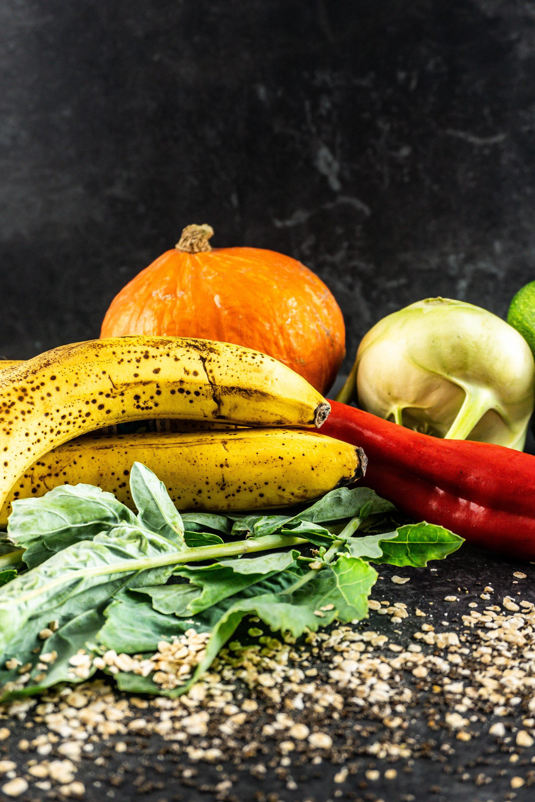 Bananas in focus with pumpkin, kohlrabi, and pepper visible in the background