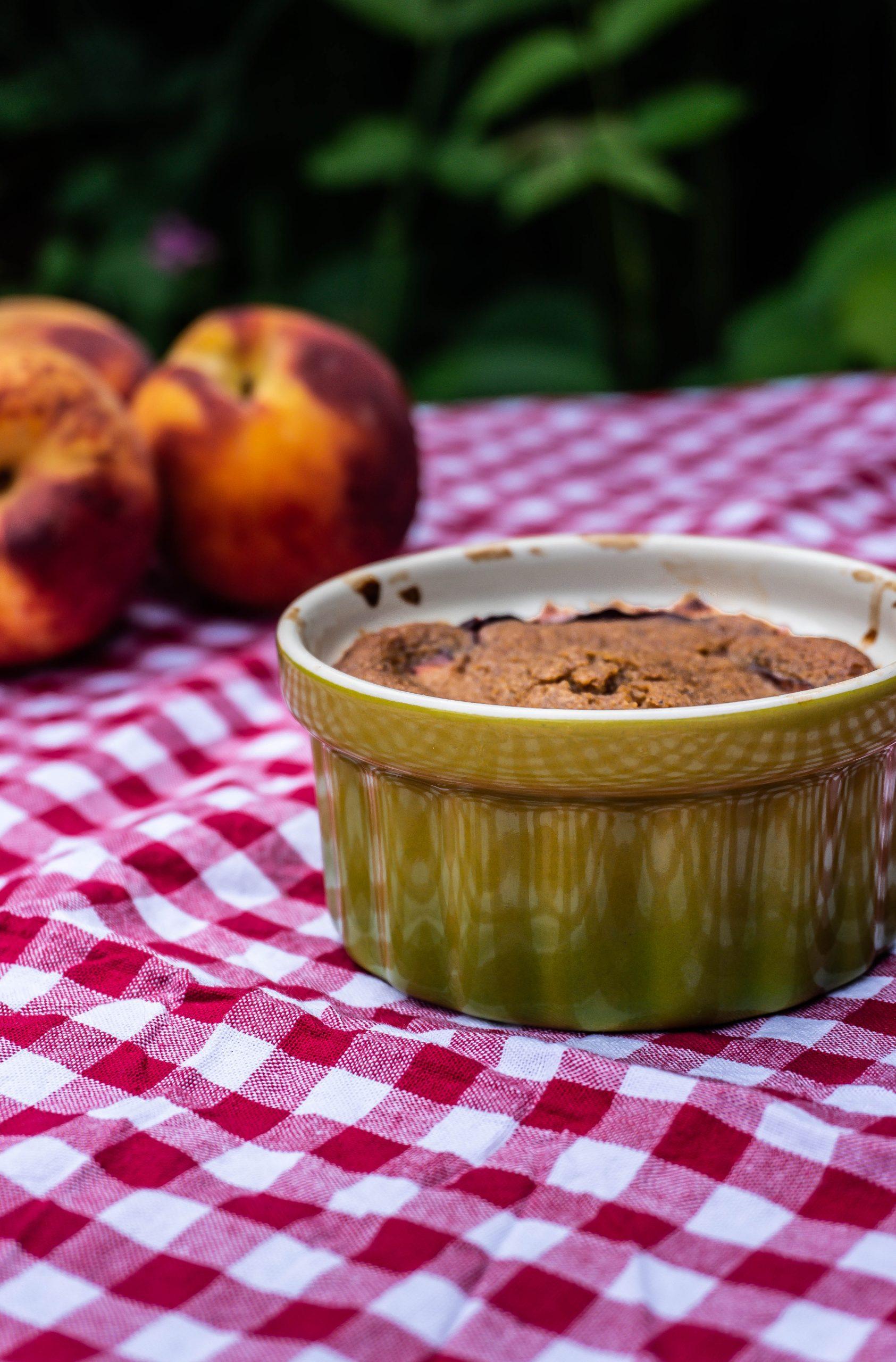Mini Peach Cobbler in a small ramekin with peaches in the background