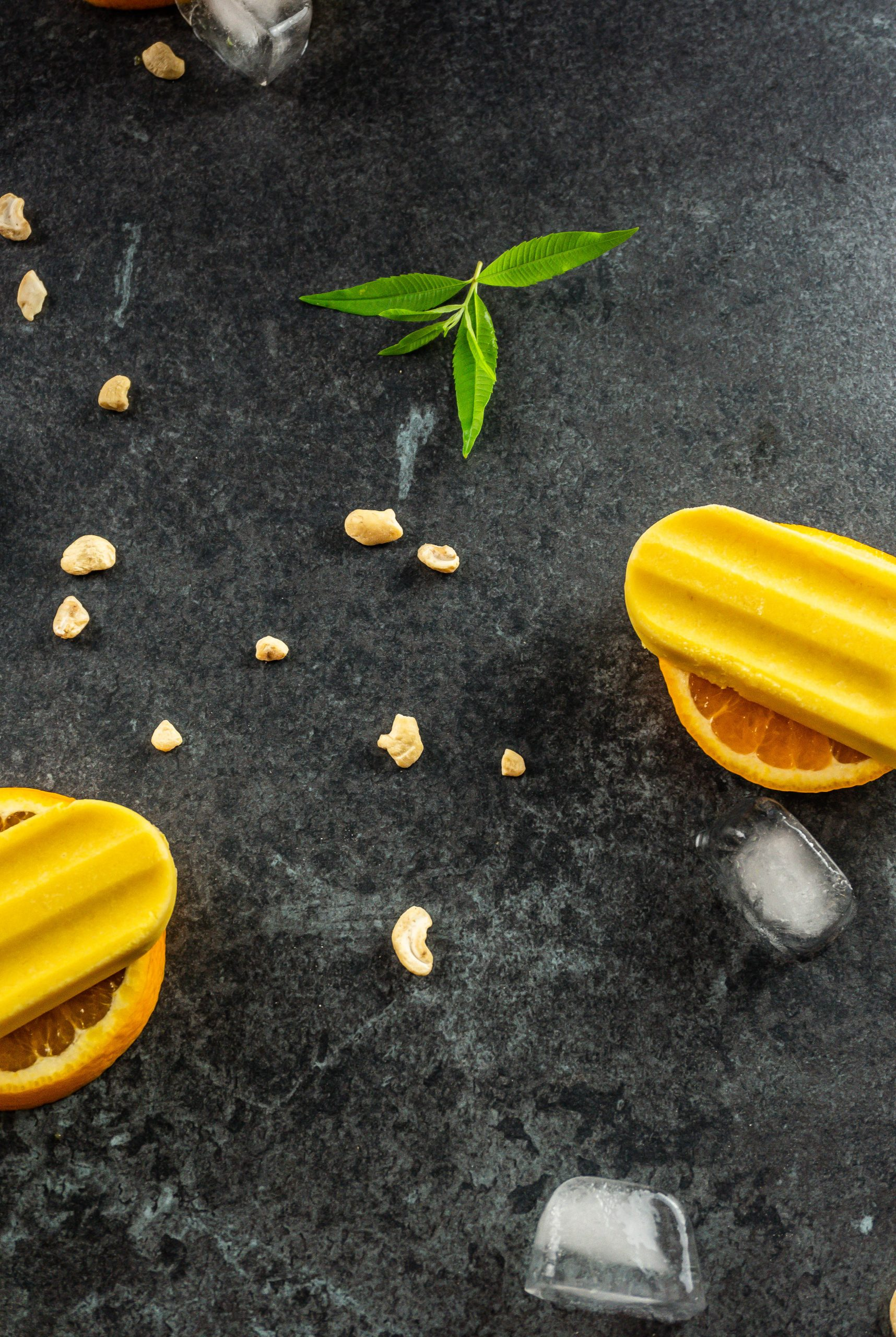 Scattered cashews in focus surrounded by Orange Creamsicle Popsicles