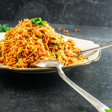 Simple Carrot Salad on a plate with a spoon and fork stuck into it, photographed on a dark background photographed from a side angle