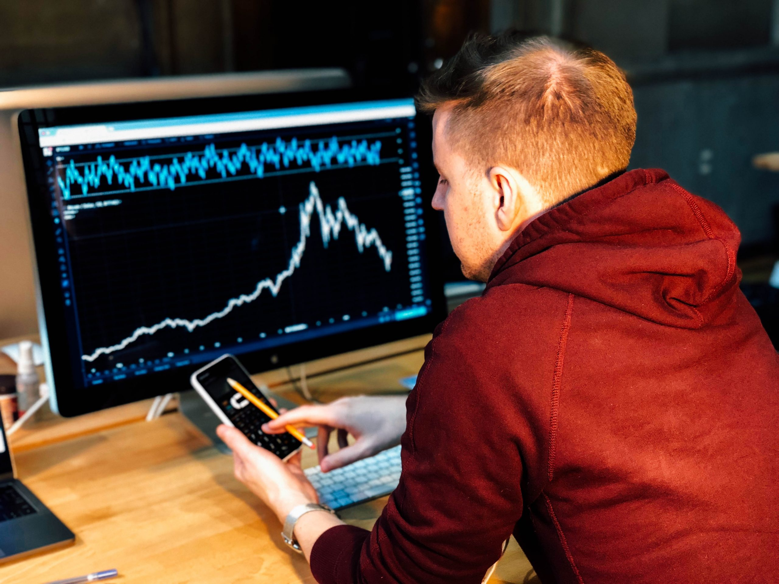 Man sitting in front of a screen with stock indices