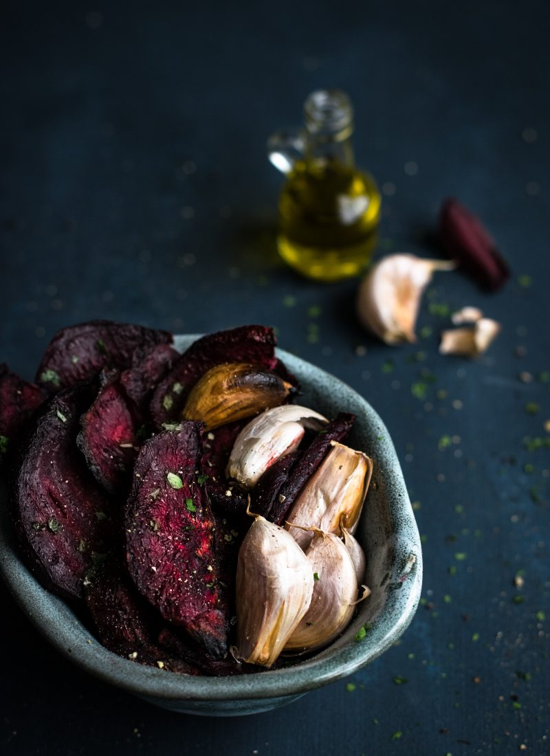 A bowl with roasted beet root and garlic with olive oil, beets and garlic visible in the background