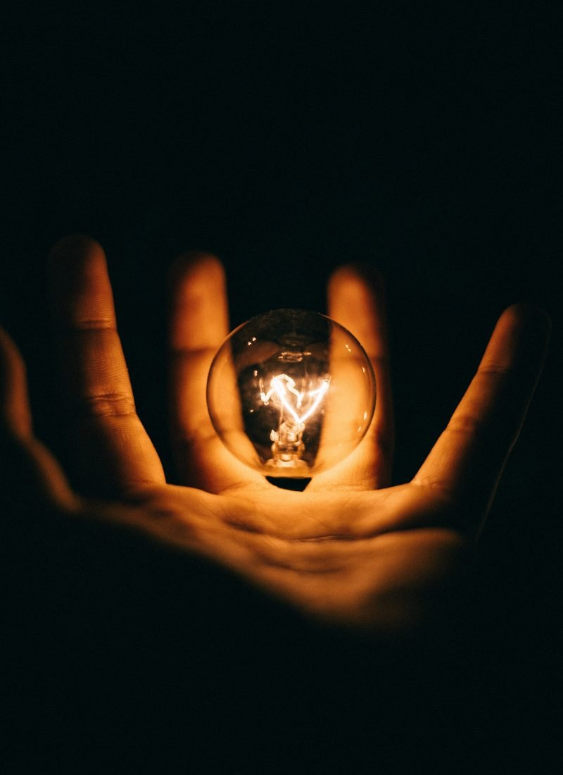Light bulb fizzing in an open hand