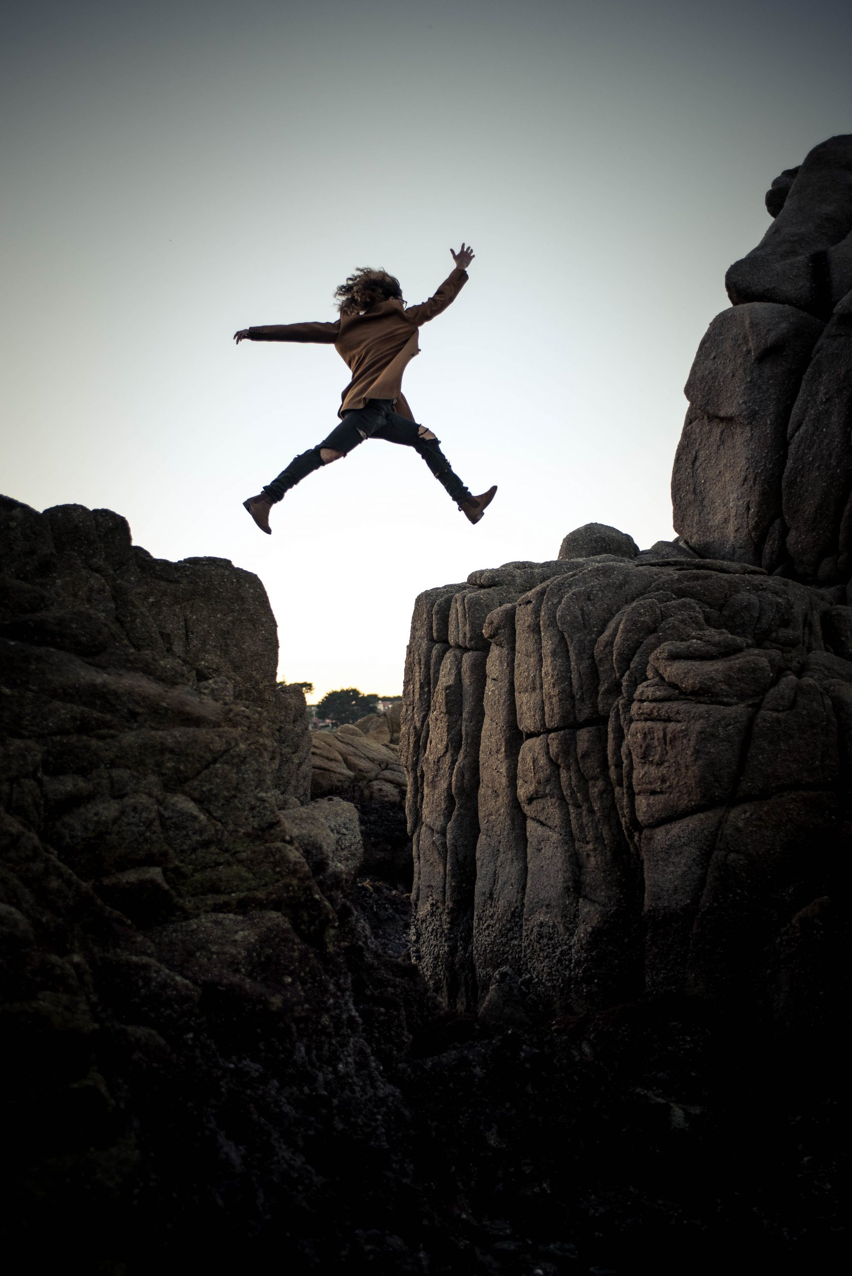 Female jumping over a cliff