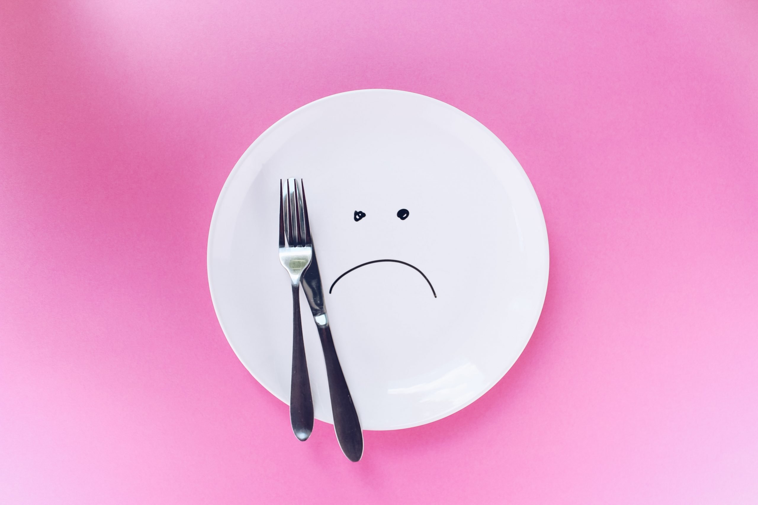 An empty plate with a downward smiley drawn on it