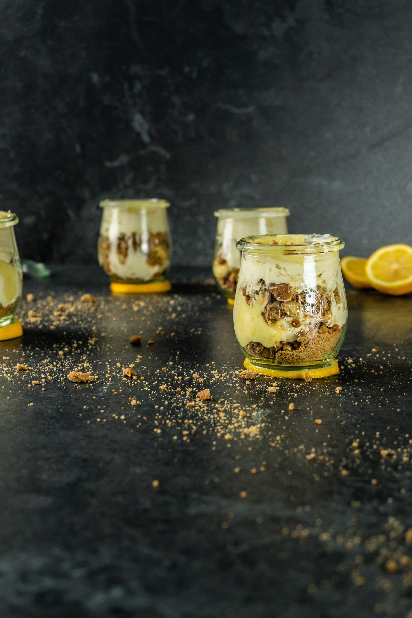 Easy Lemon Cheesecake Cups on a dark background with crunchy ginger cookies crumbled around them