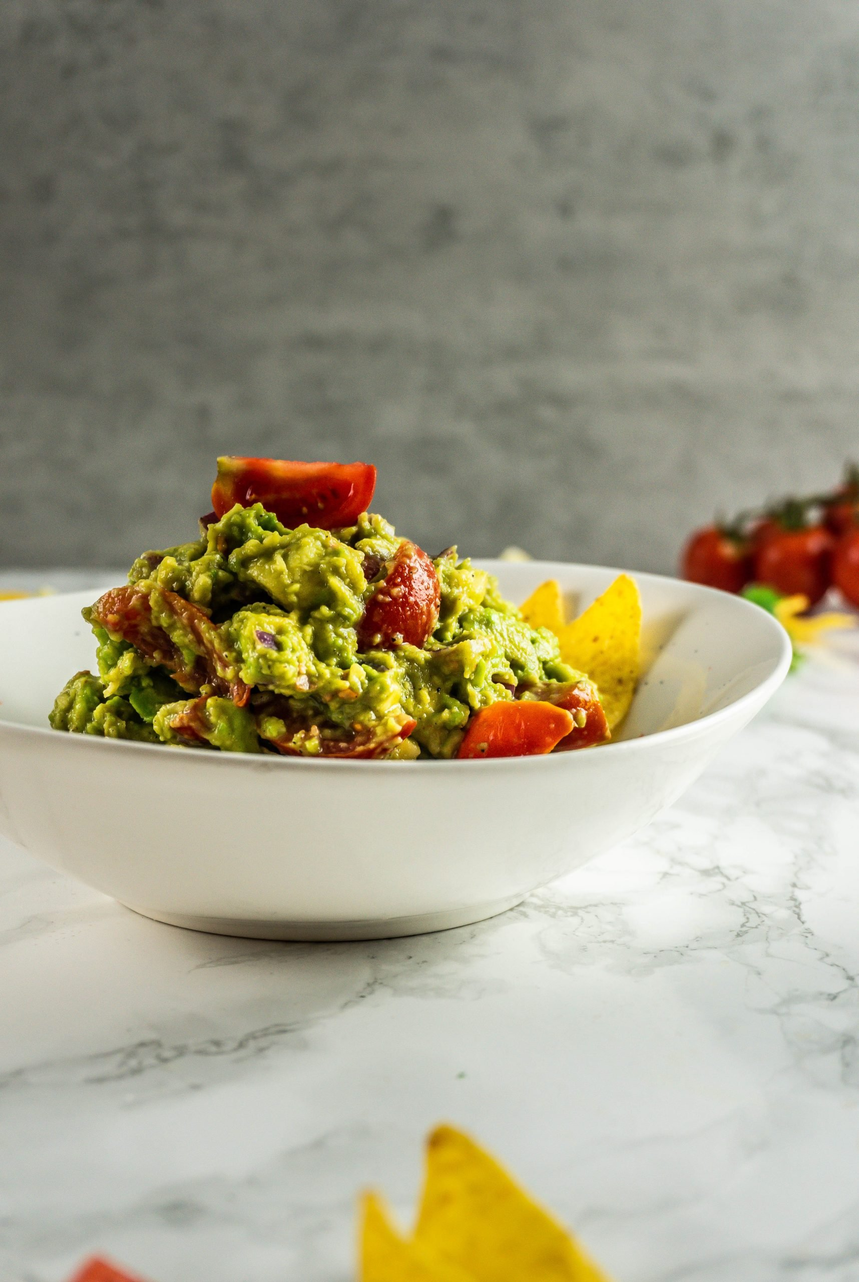 My Dear Friend's Best Guacamole in a bowl with tortilla chips, halved tomatoes, and cilantro scattered around, photographed from a side angle