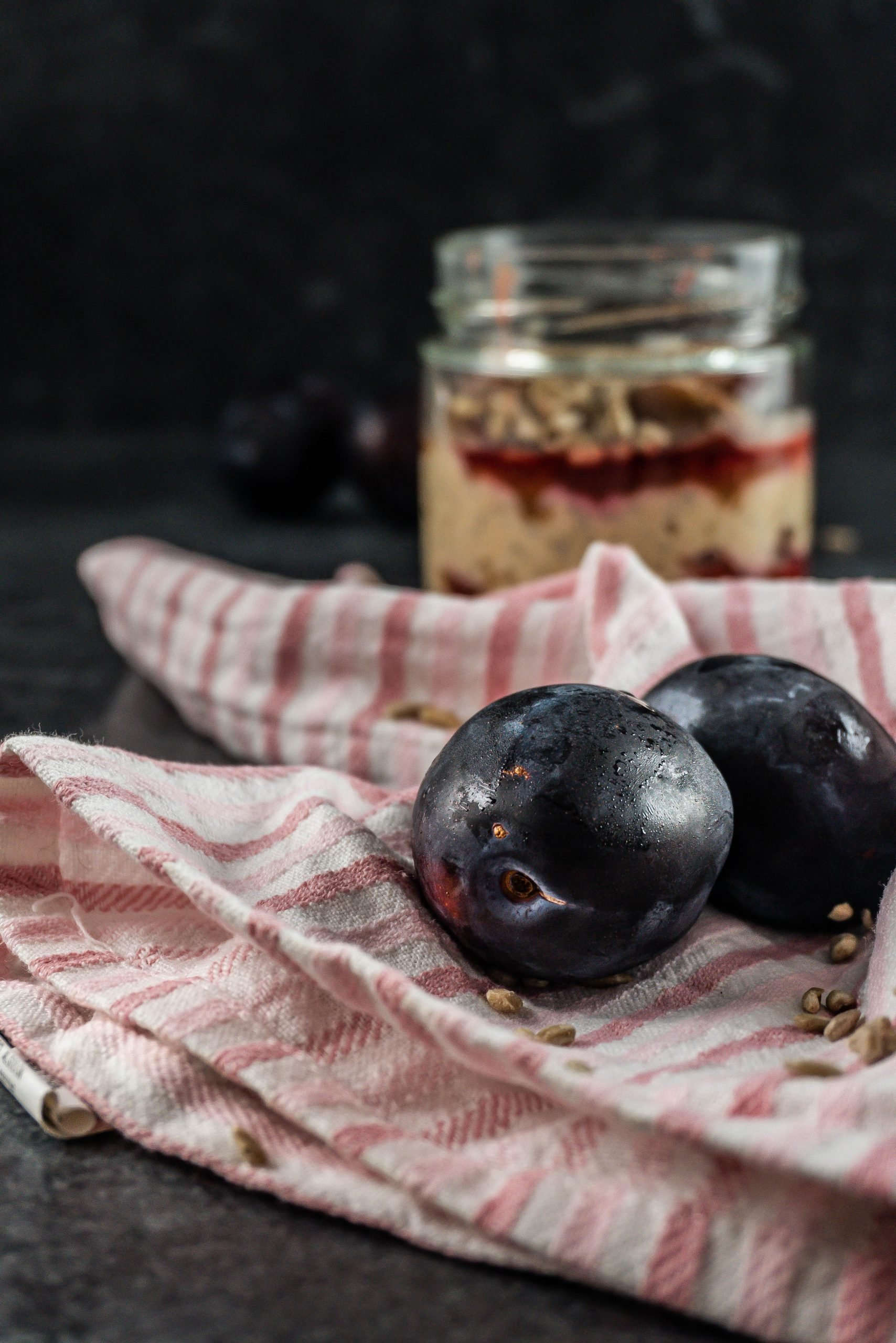 Plums in a pink striped tea towel with Spiced Overnight Oats in a glass jar in the background