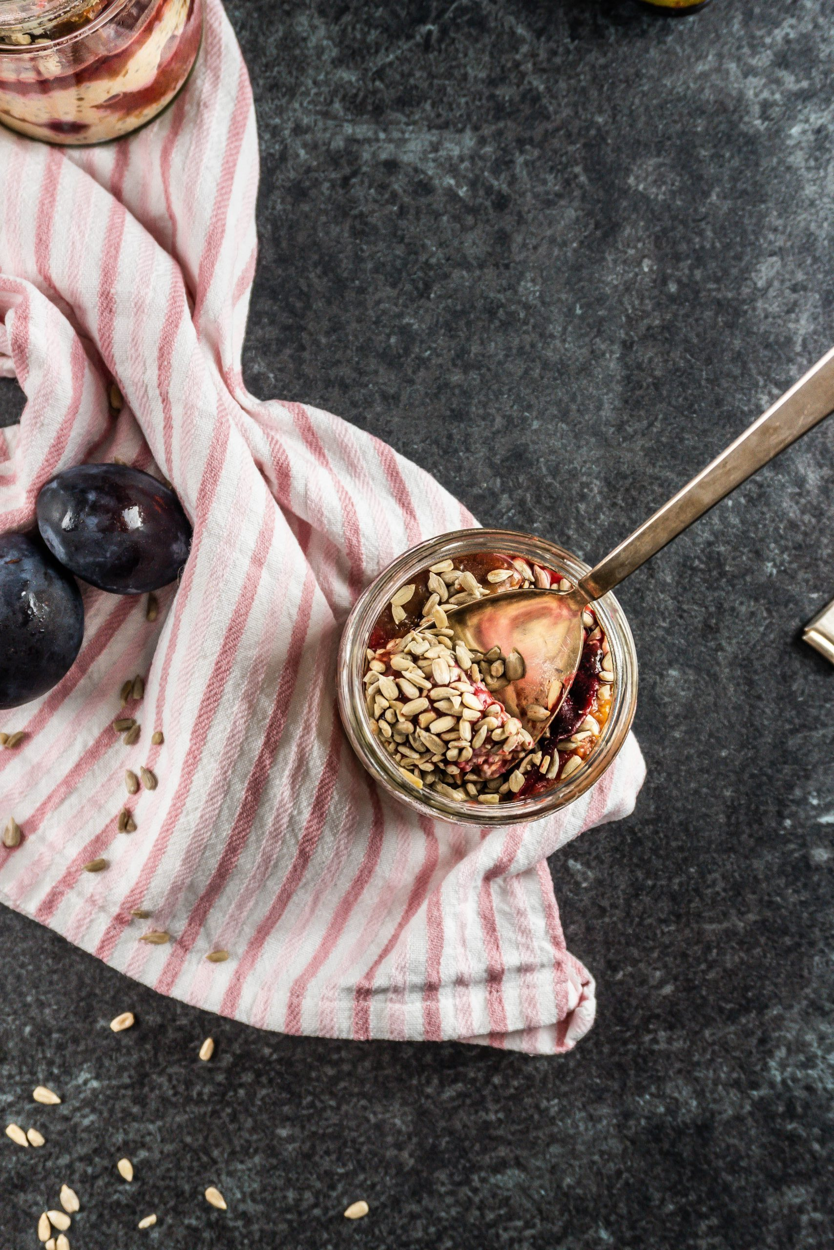 Spiced Plum Overnight Oats photographed from above with a spoon stuck into it