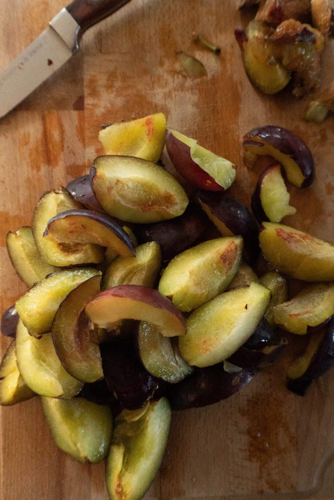 Plums cut into quarters on a chopping board