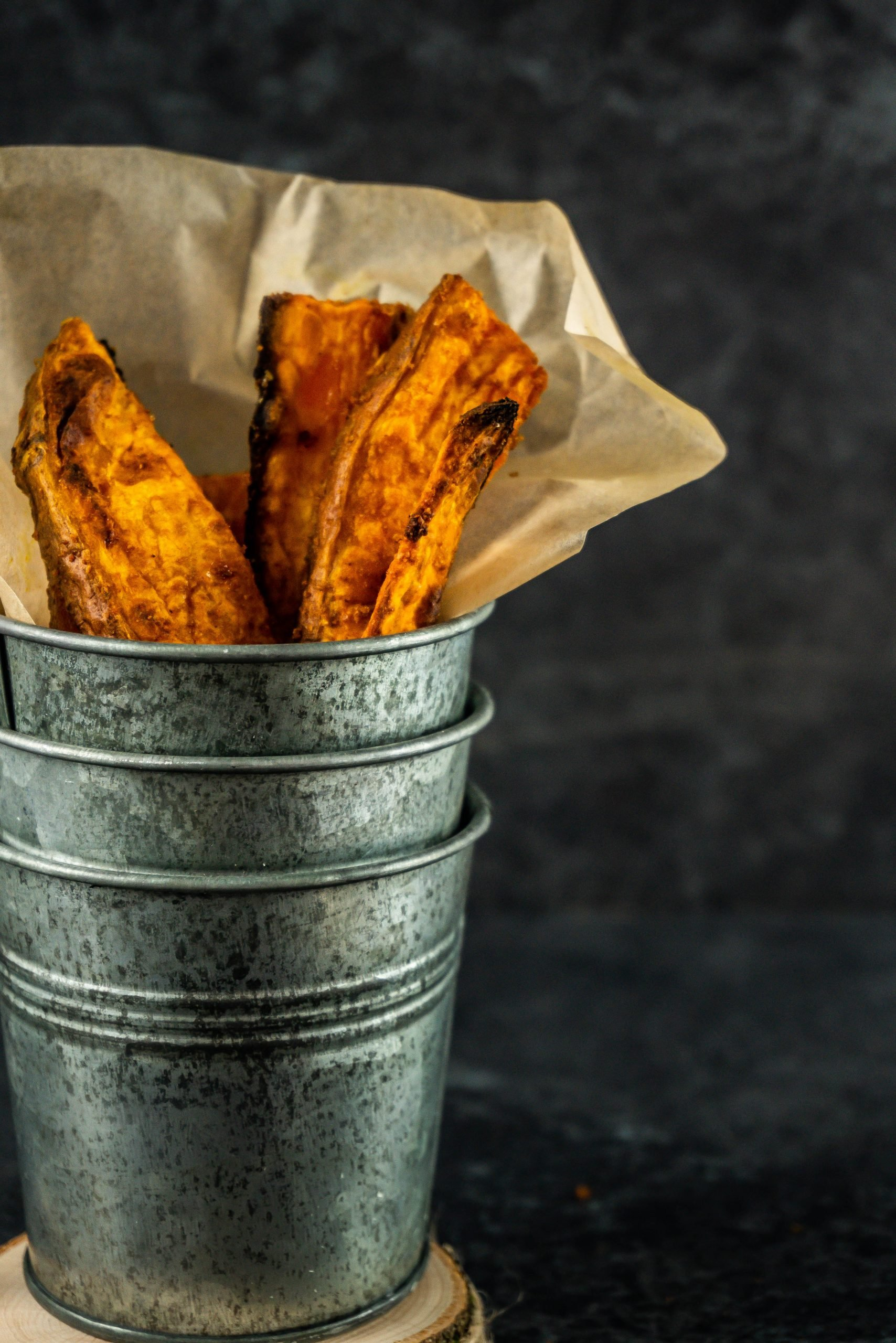 Sweet Potato Wedges in a metal cup being stacked up photographed up close