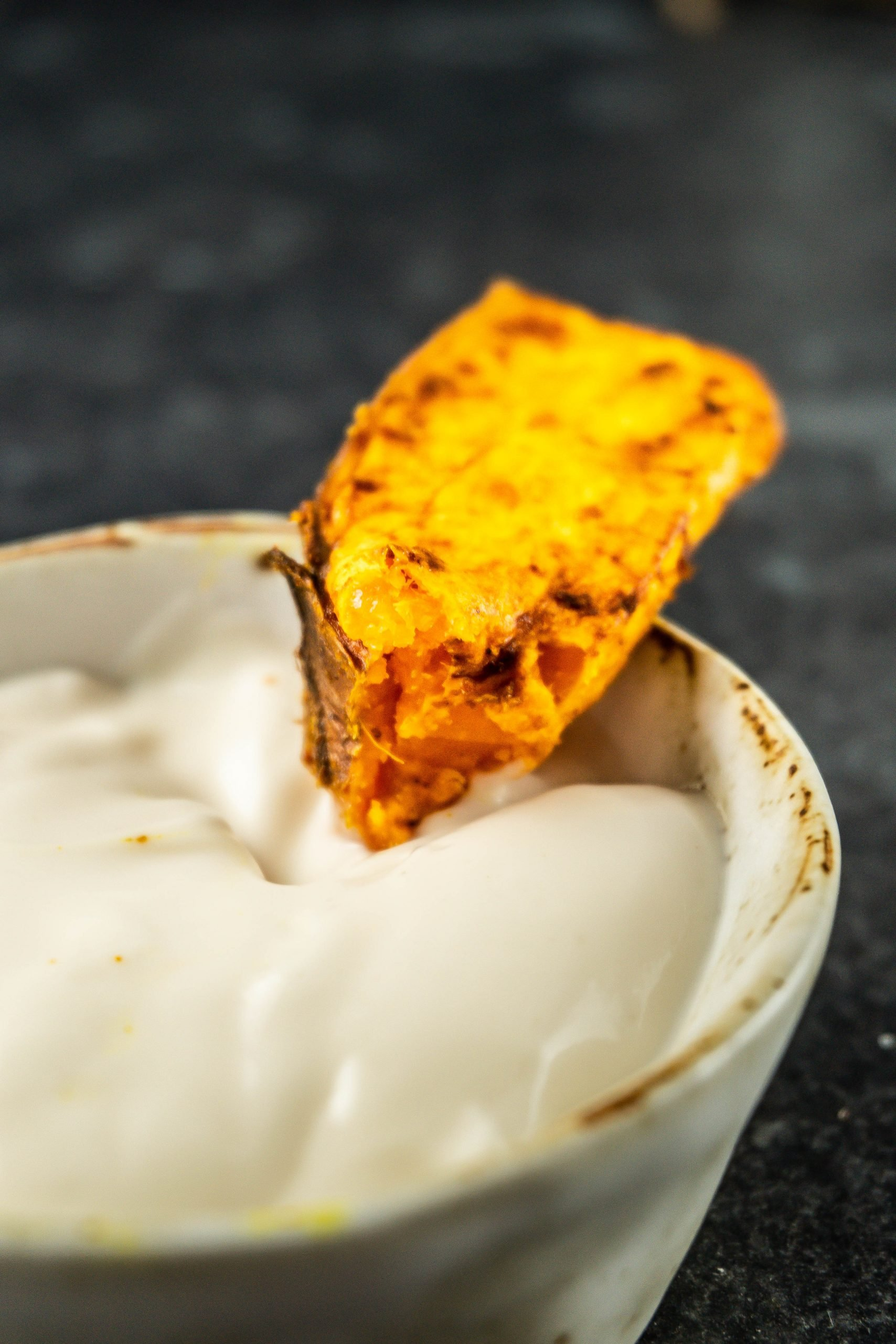 Sweet Potato Wedges being dipped into mayonnaise