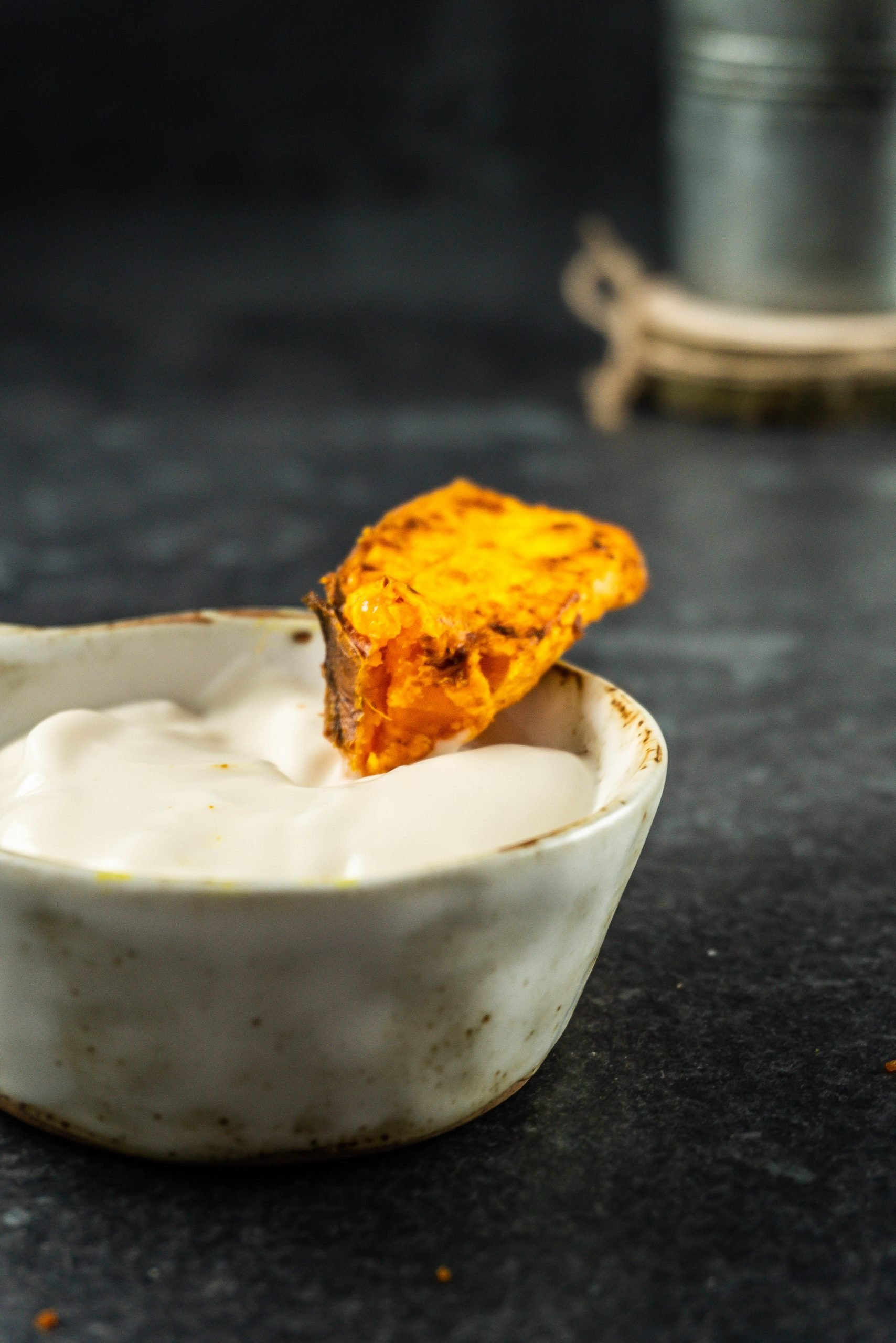 Sweet Potato Wedges being dipped into mayonnaise, photographed from a side angle