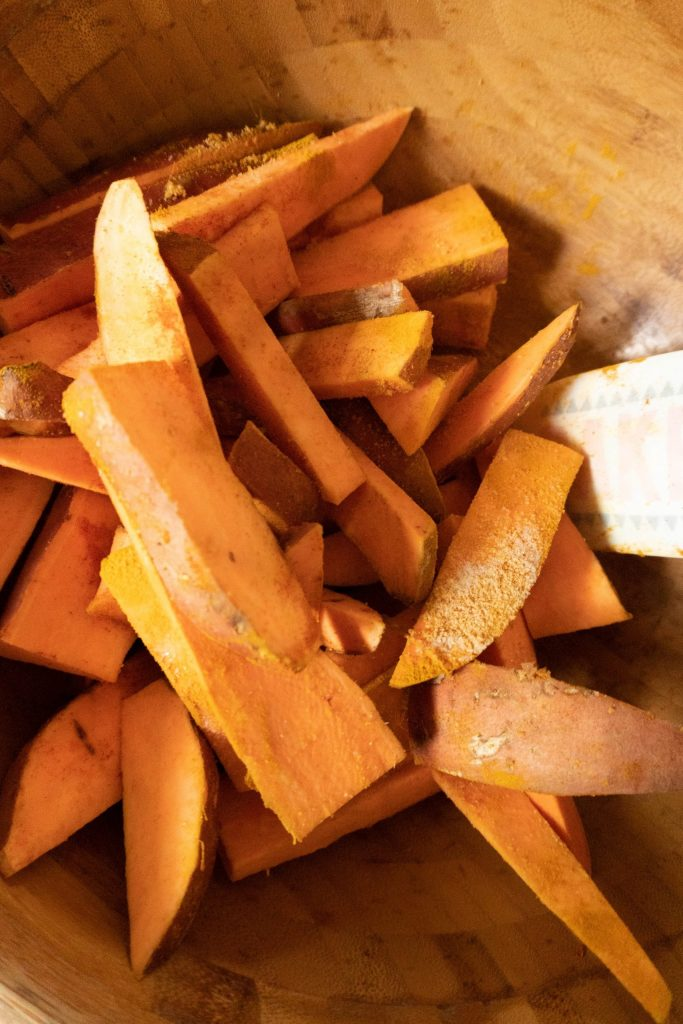 Sweet potatoes cut into wedges being covered in a bowl with spices