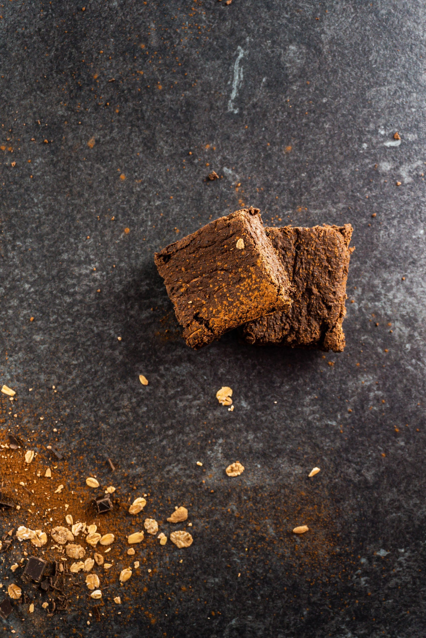 Vegan and Gluten-free Zucchini Brownies on a dark background surrounded by scattered cocoa powder, chocolate pieces, and oats